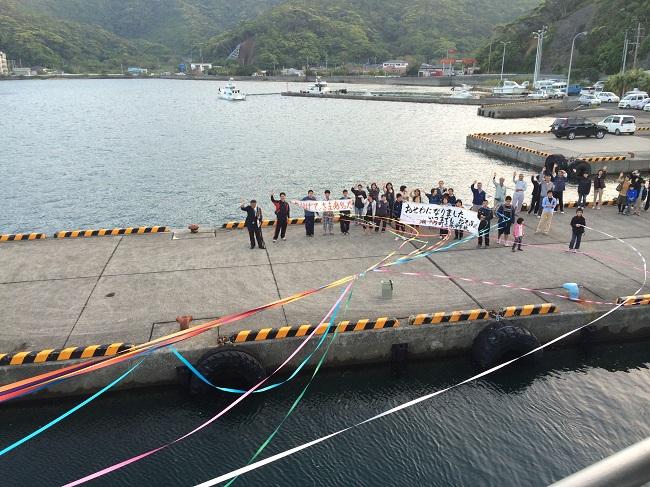 船から見た見送る人々。風になびき次第にちぎれていくテープ。
