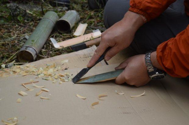 樹皮を剥ぐための竹ベラを作成中。