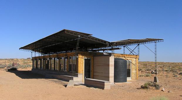 建物を別の角度から、雨水を貯める黒いタンクが見える Via:designbuildbluff.org