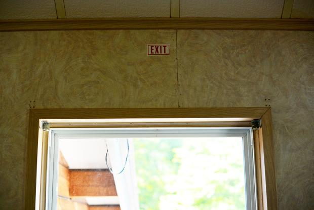 壁のクロスを剥がしてみたら、窓の上にEXITと書かれていることを発見!