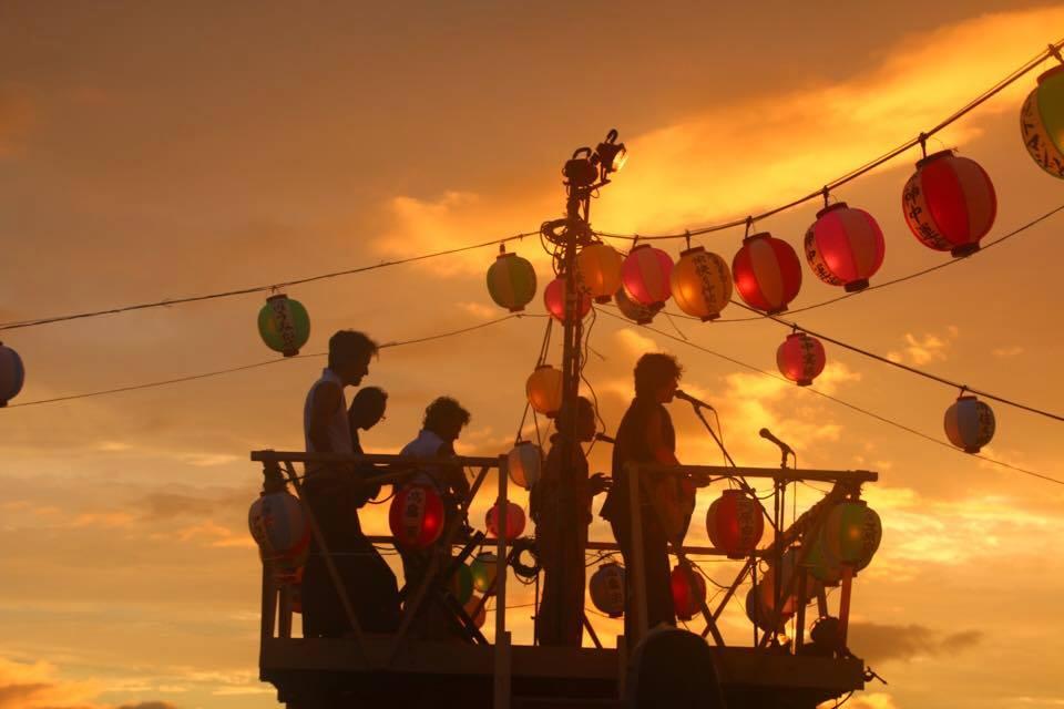 鎌倉・材木座の盆踊り大会で砂浜に組まれた櫓の上で演奏する小川コータさん