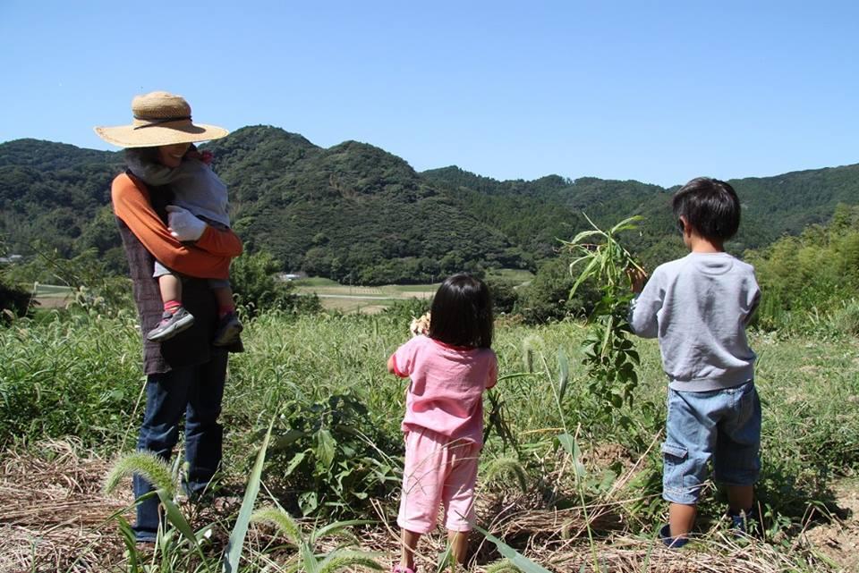 南房総の里山の前に佇む馬場さんと3人の子供たち
