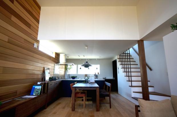 大きな窓とキッチン背面の窓によって、挟まれたLDK。壁面にスッと伸びる木のラインがモダンで高級な印象