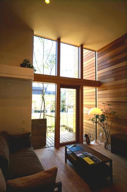 ウッドカーテンに縁取られた窓が天井まで続くリビングは、まるで高原のリゾートホテルのよう。
